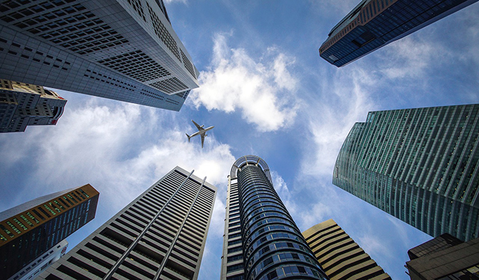 an upward view of an airplane between skyscrapers in Singapore