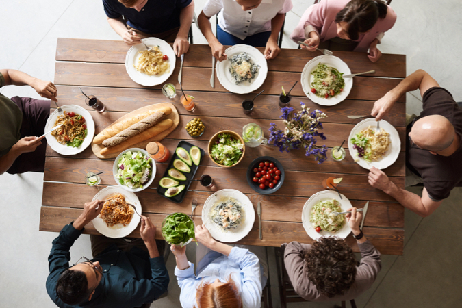 A group of travelers using the sharing economy to have a meal together