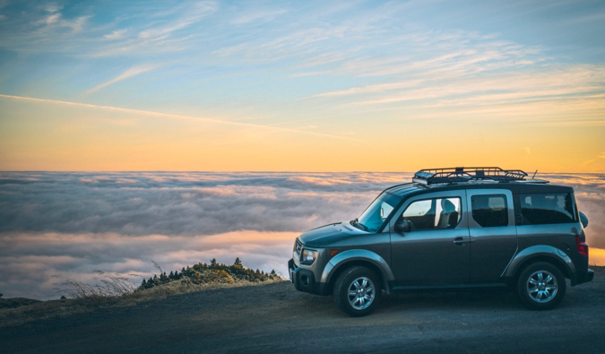 A car rental parked near a beautiful view surrounded by clouds