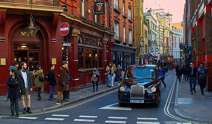 busy Soho with a black cab and people in the street; photo by Pedro Szekely (flickr:@pedrosz)
