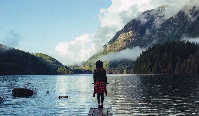 a woman standing at the end of a dock overlooking an alpine lake