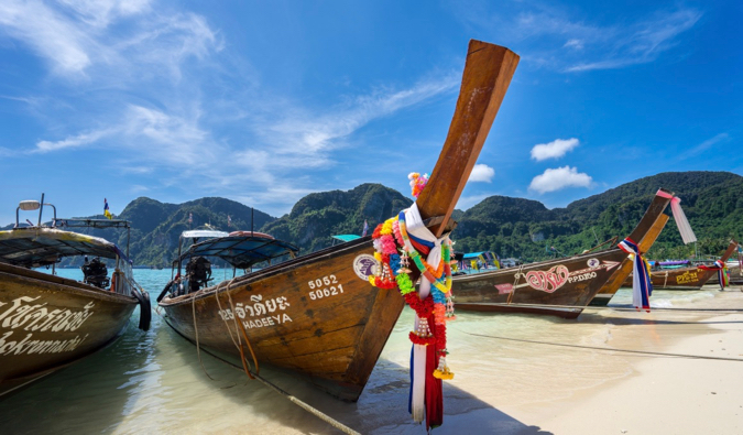 The longtail boats of Koh Phi Phi parked in the sand in front of a bright blue sky in Thailand