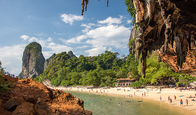 a sunny beach view in Thailand framed with rocky outcrops