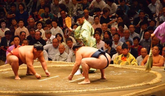 Deux lutteurs de sumo sur le point de se battre dans une arène massive sous le regard de la foule au Japon
