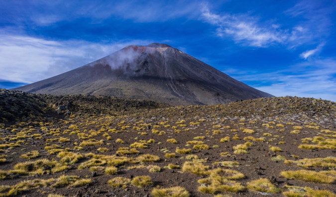 A blue sky above the dark, steep slopes of Mount Ngauruhoe in the Tongariro Alpine Crossing in New Zealand