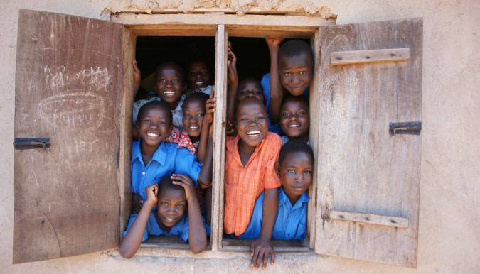 Smiling school children in Africa looking out of a classroom window