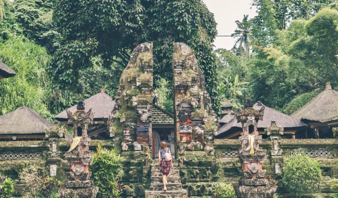 A solo female traveler exploring a temple in Asia