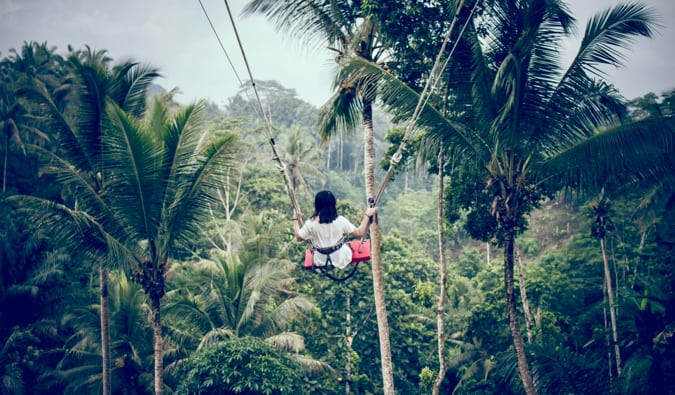 A solo female traveler on a swing in Bali in the jungle