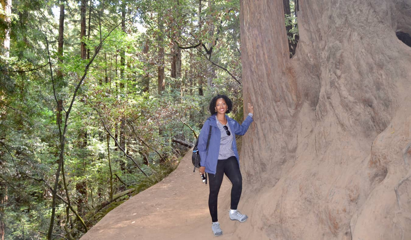 Senitra, a solo black female traveler posing by a huge tree