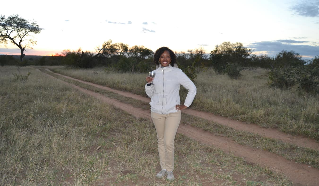 Senitra, a solo black female traveler posing while on safari in Africa