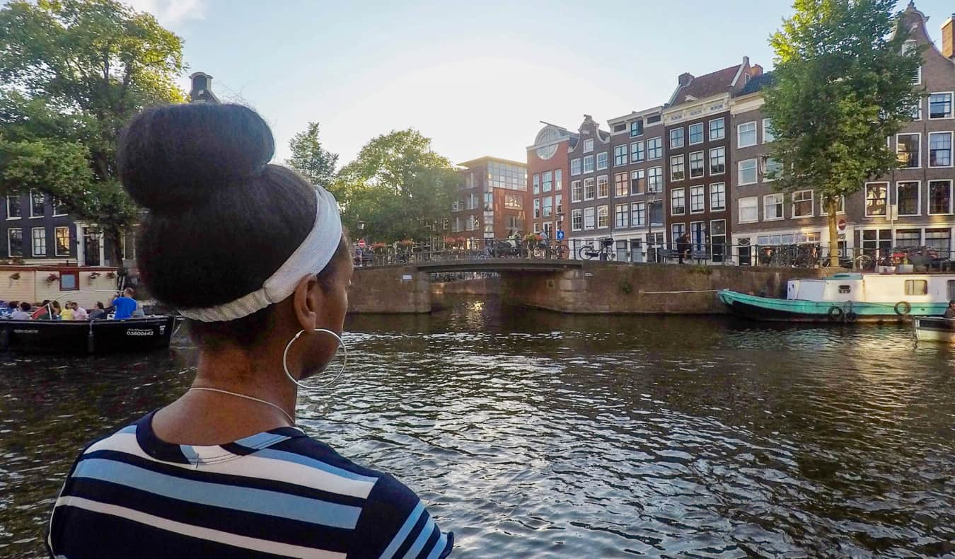 Senitra, a solo black female traveler posing near a canal in Europe