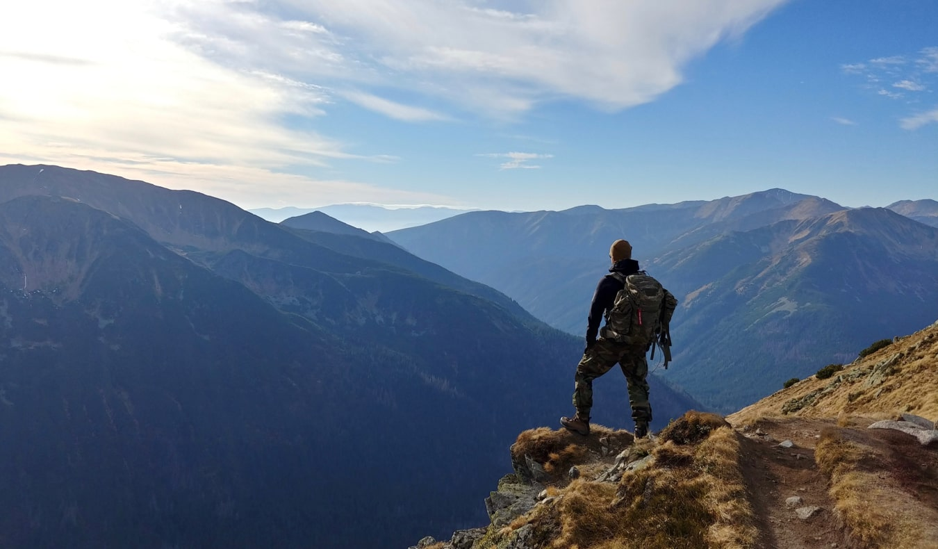 A solo traveler standing on the edge of a cliff looking in the distance