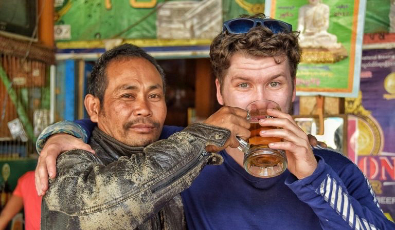Will from The Broke Backpacker blog posing with a local in Asia