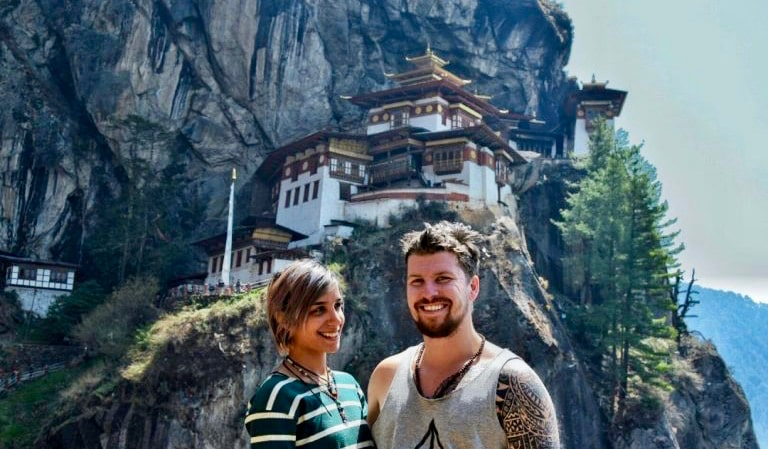 Will from The Broke Backpacker posing with his girlfriend in Bhutan near the Tiger's Nest