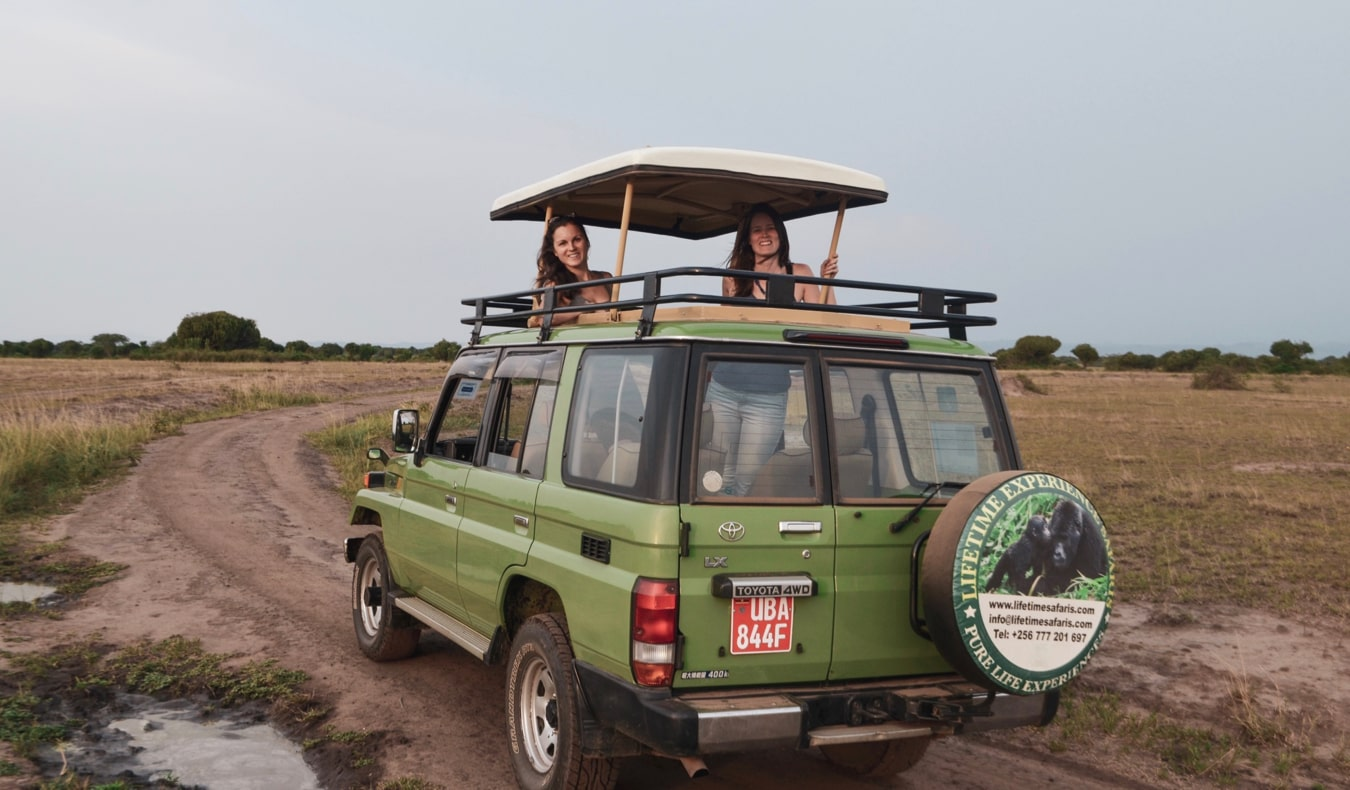 Two female travelers on safari in Uganda standing in a jeep