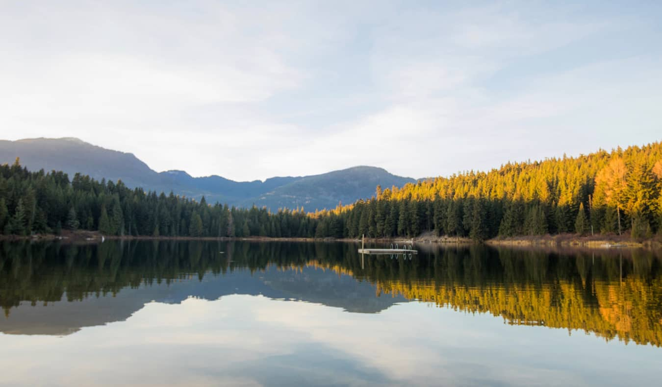 A calm lake with a small floating dock near Whistler, BC, Canada