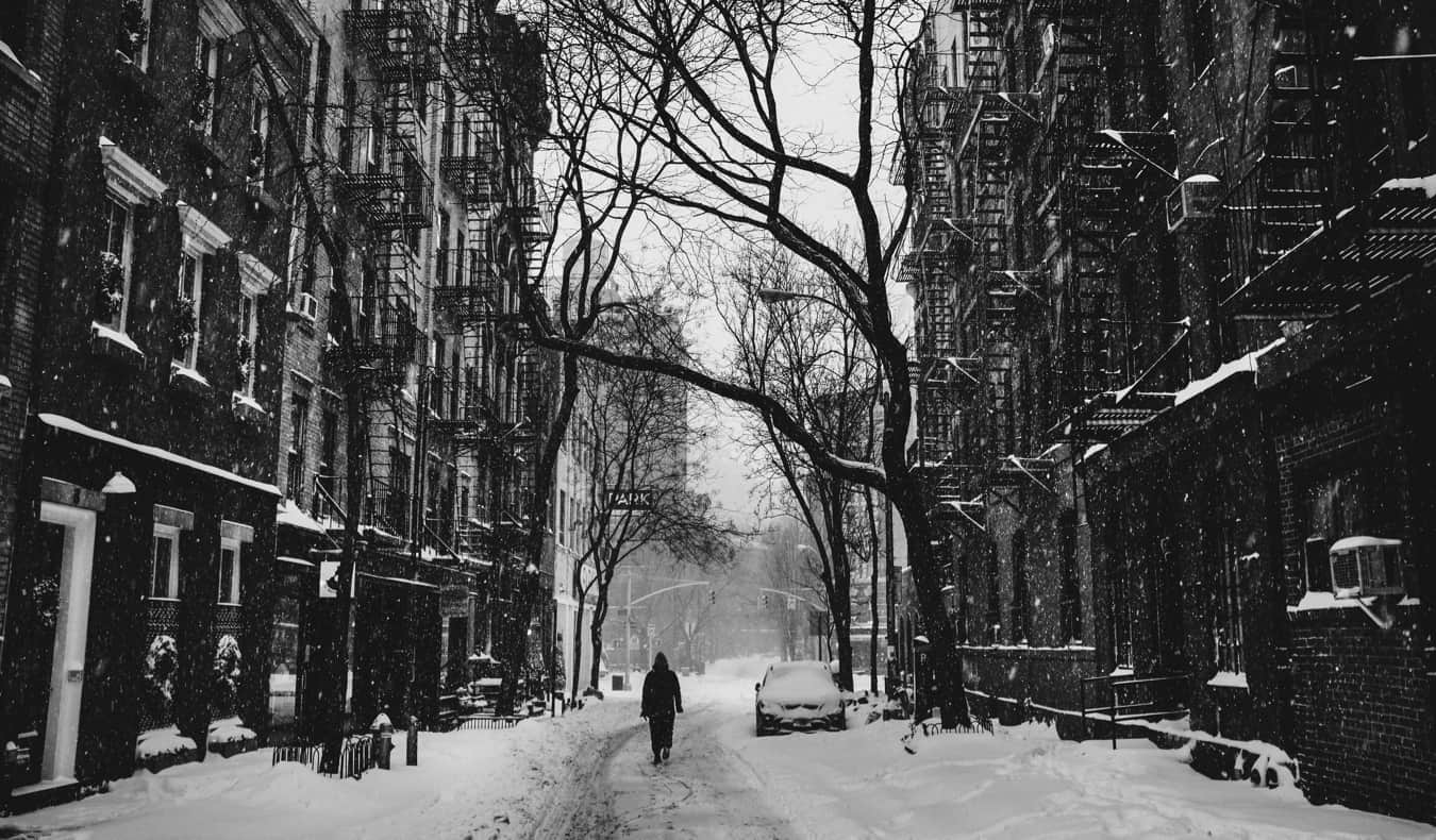 Black and white photo of someone walking in the snow in NYC
