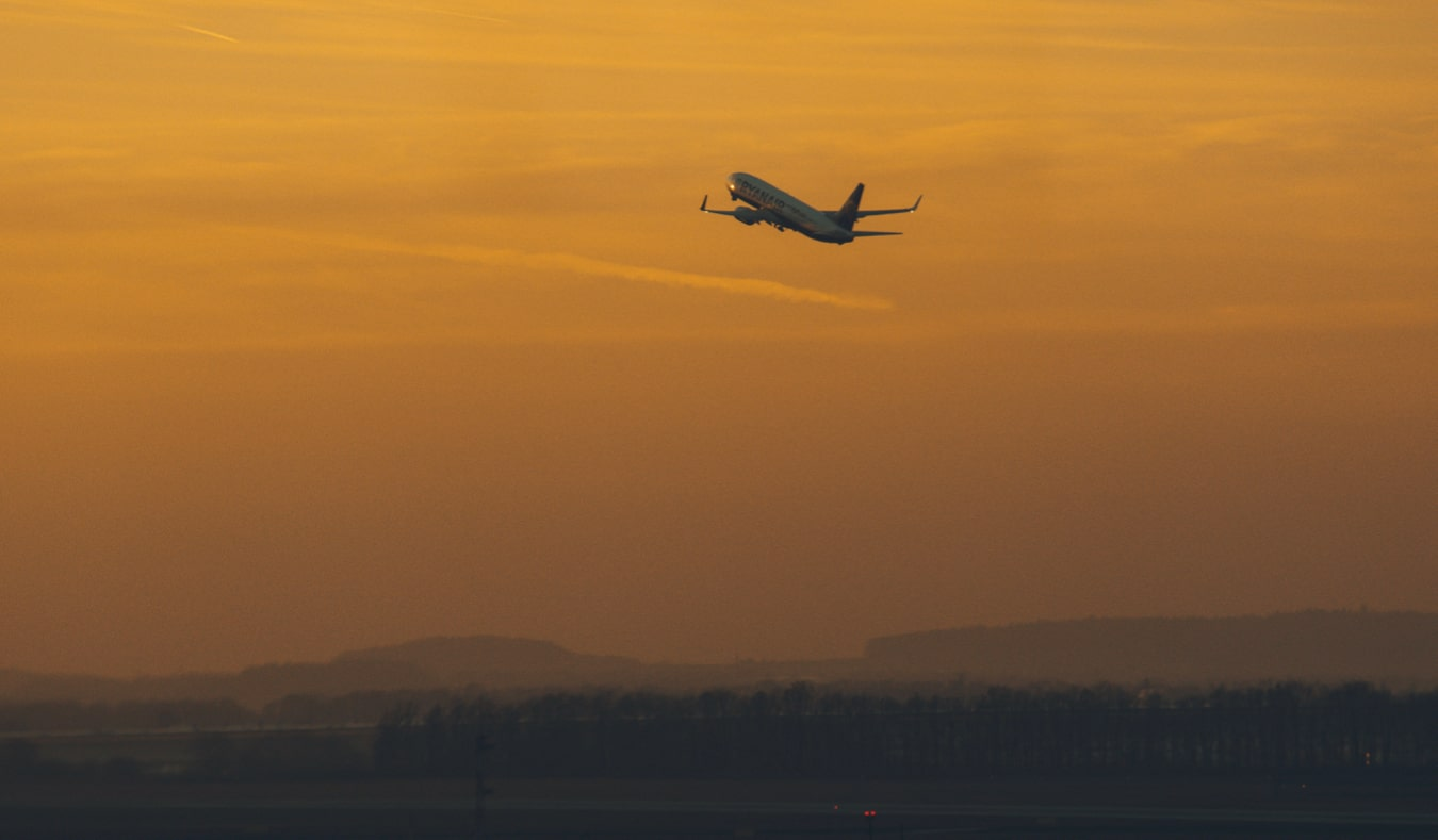 An airplane taking off during a bright orange sunset