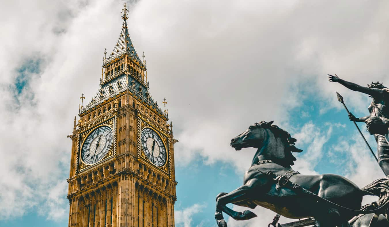 A close-up shot of Big Ben with a statue in the foreground in London, England