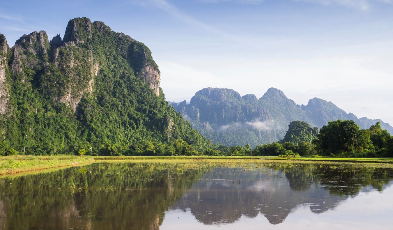 A serene river passing by the mountains in Laos