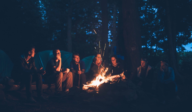A gorup of friends and travelers sitting by a fire at night