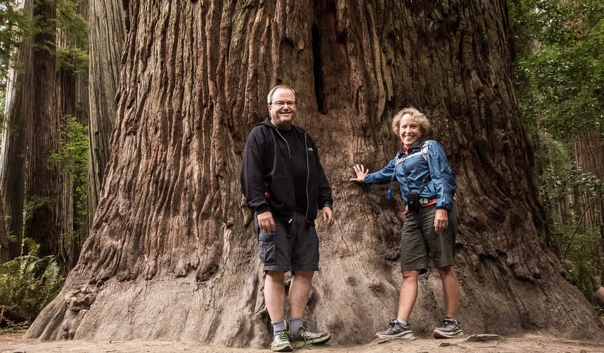 Tom and Kristin, two retired senior travels posing near a redwood tree