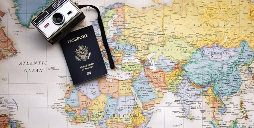 A map of the world with a camera and passport resting on it