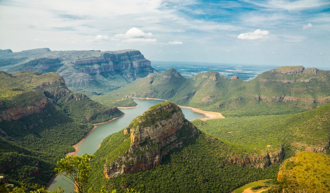 A sweeping view of lush hills and mountains and the ocean in South Africa