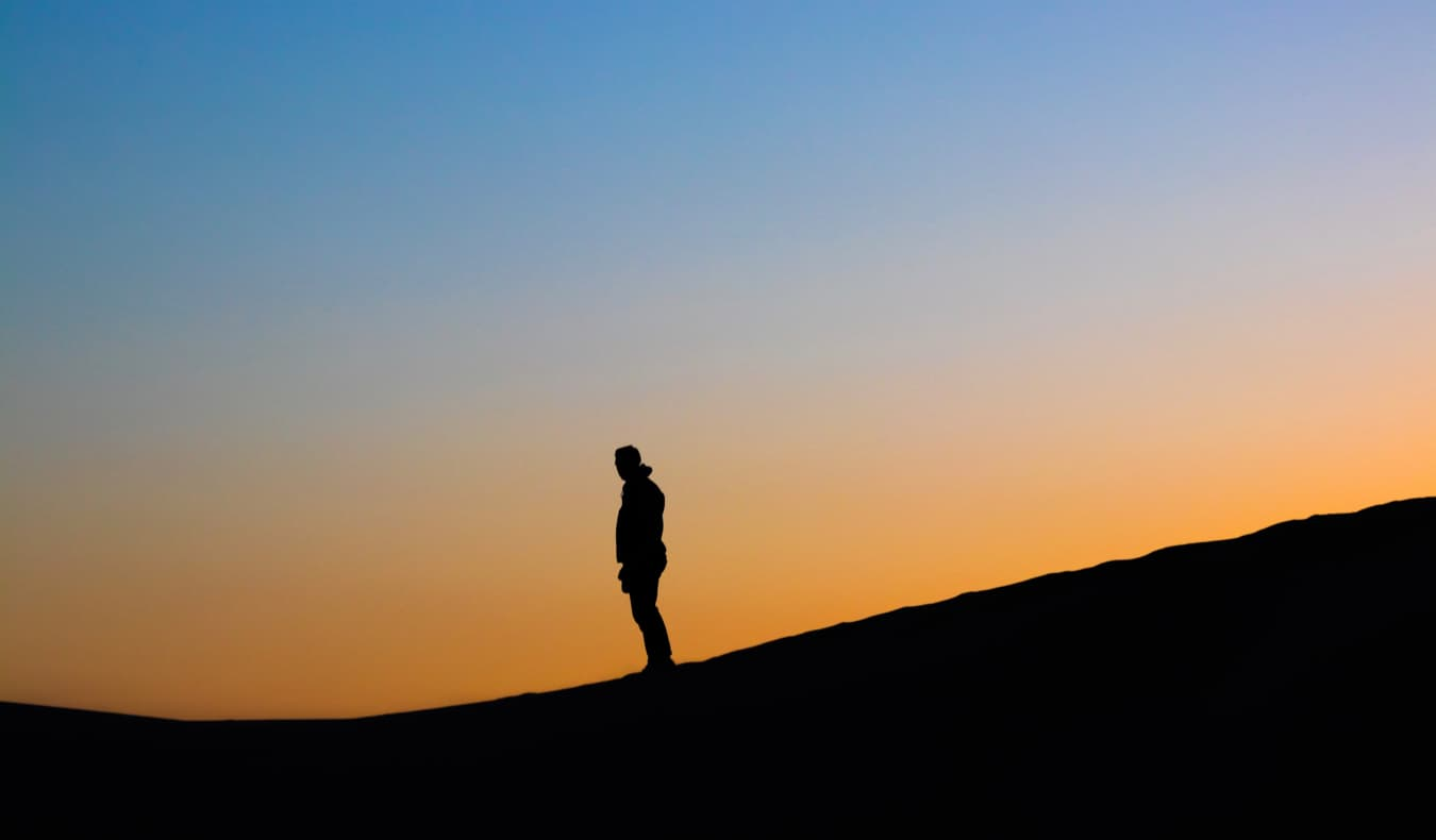 A man standing on a cliff at sunset