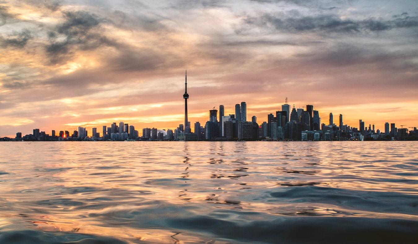 An orange sunset over the Toronto skyline in summer