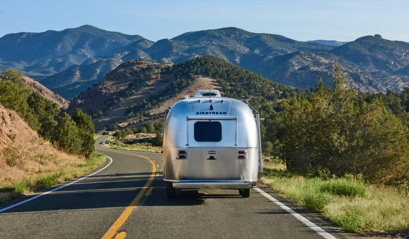 An old airstream RV crusing down the open road in the USA