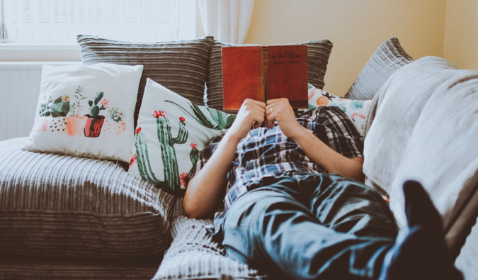 A man reading a book while sitting on his couch