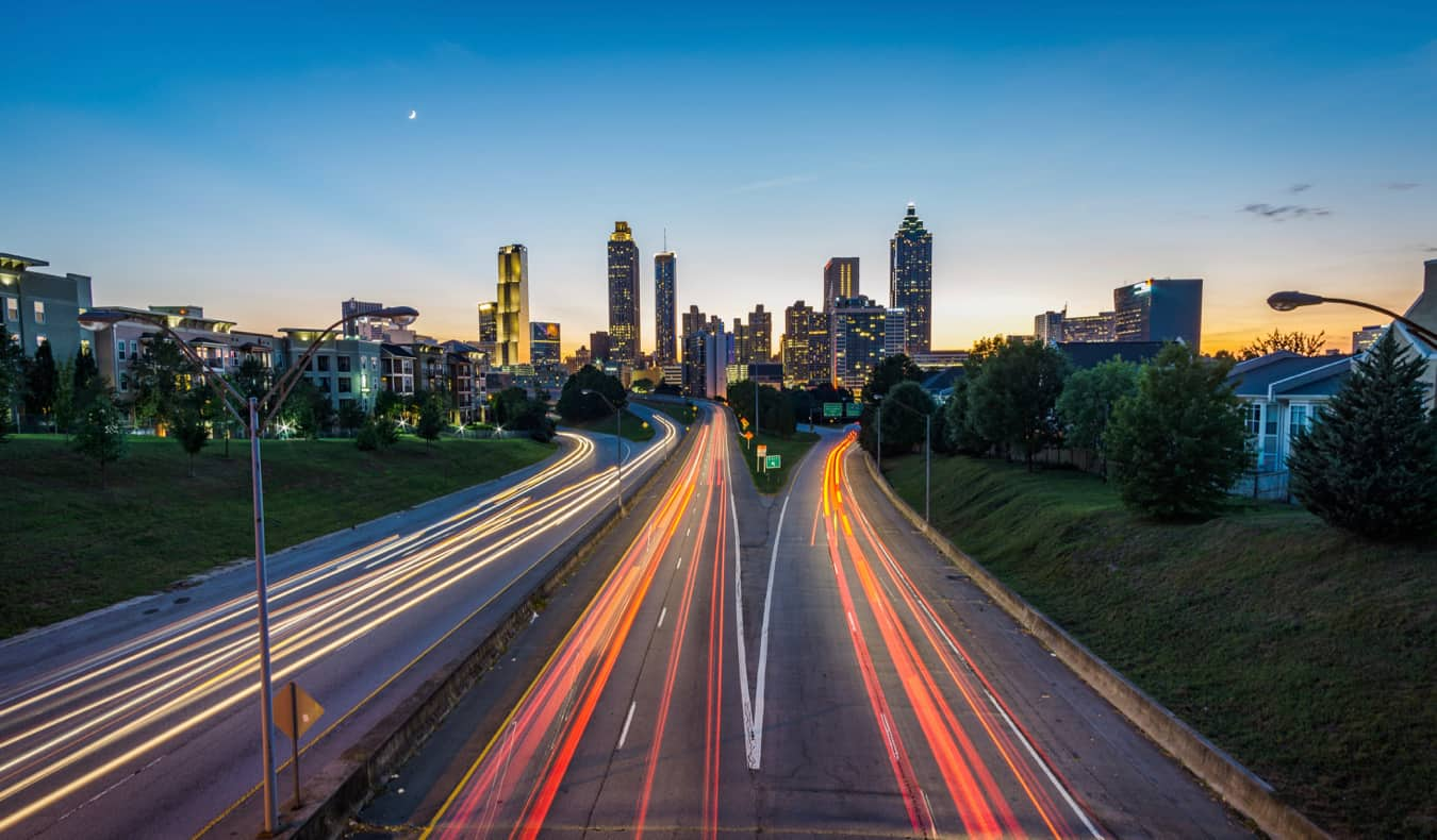 The skyline of Atlanta, GA lit up at night over the highway