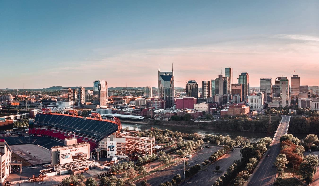 The Nashville stadium and skyline during a soft, pastel sunlight