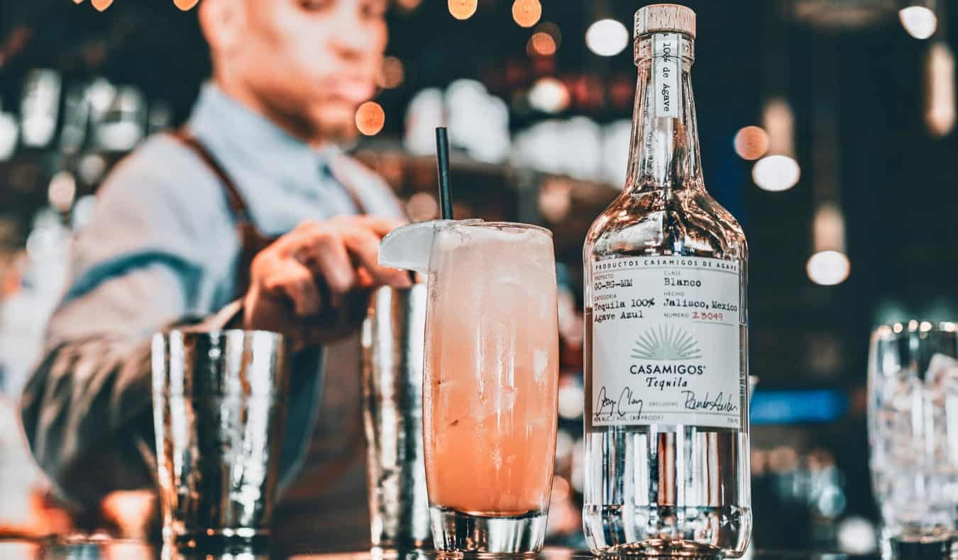 A bartender and an expensive tequila drink at a dimly-lit bar