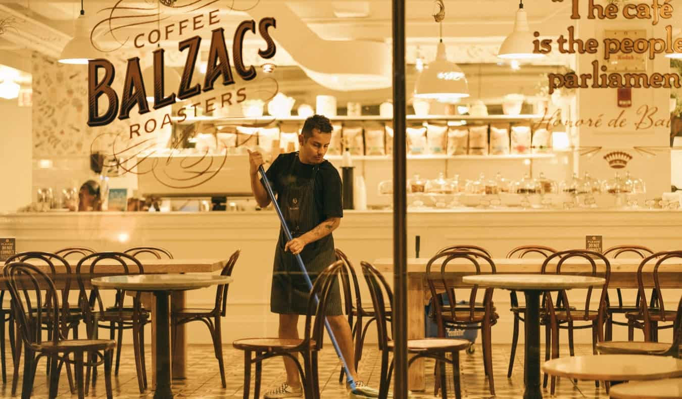 A young male worker mopping the floor at a cafe and restaurant at night