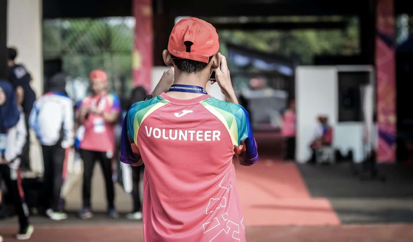 A young male volunteering at a large public event during the summer