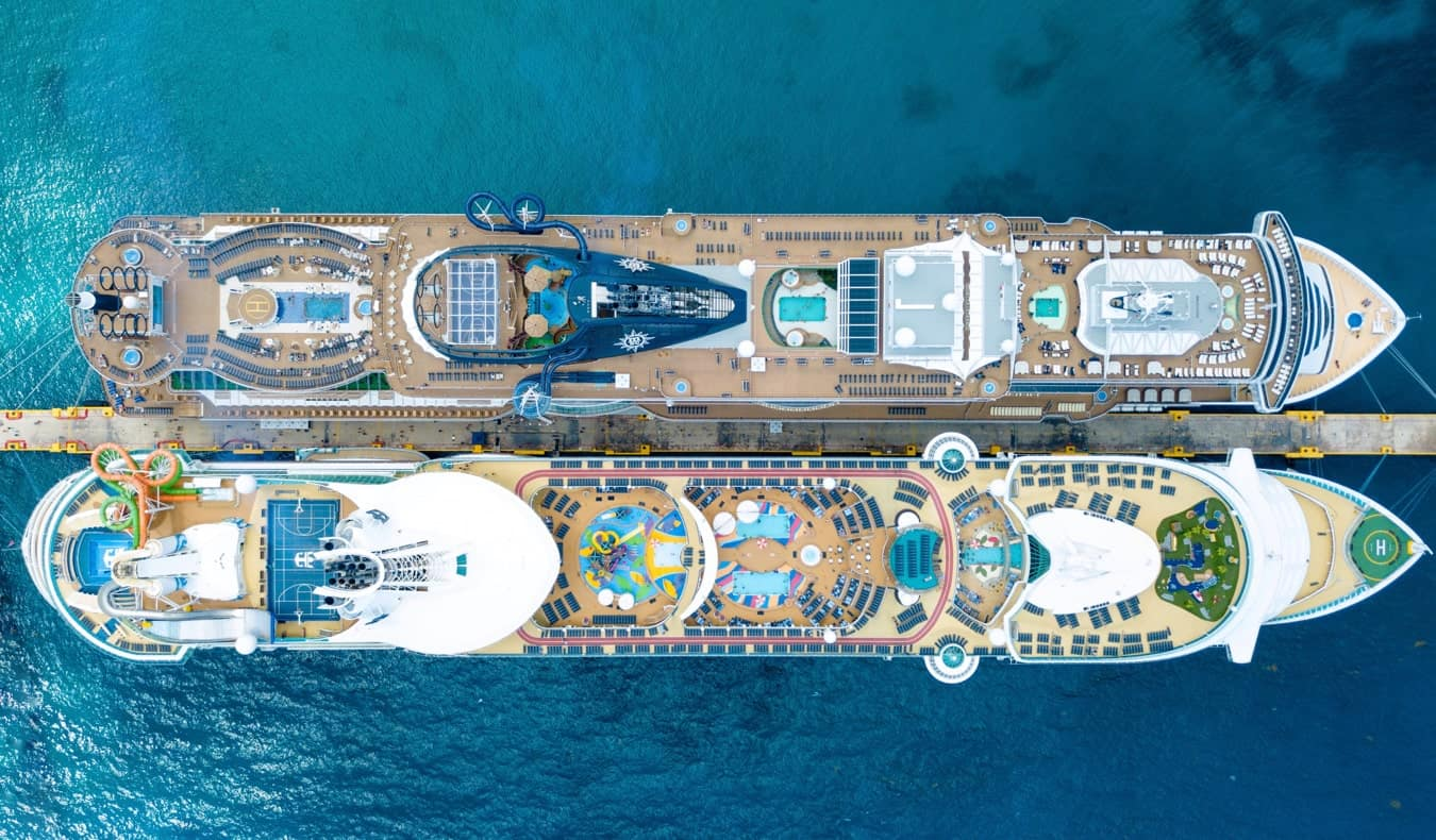 Two massive cruise ships docked side by side in the harbor