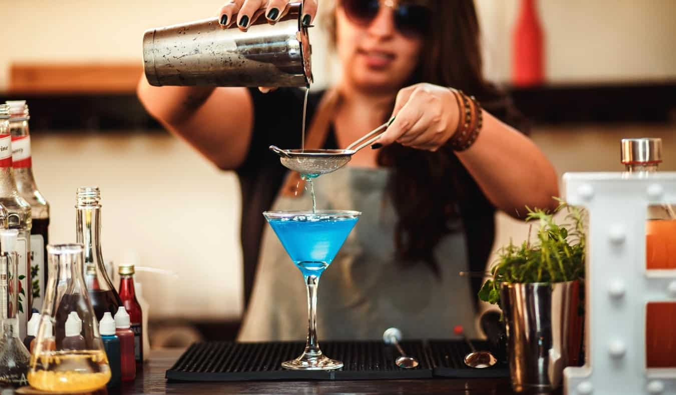 A female bartender pouring a colorful drink at the bar