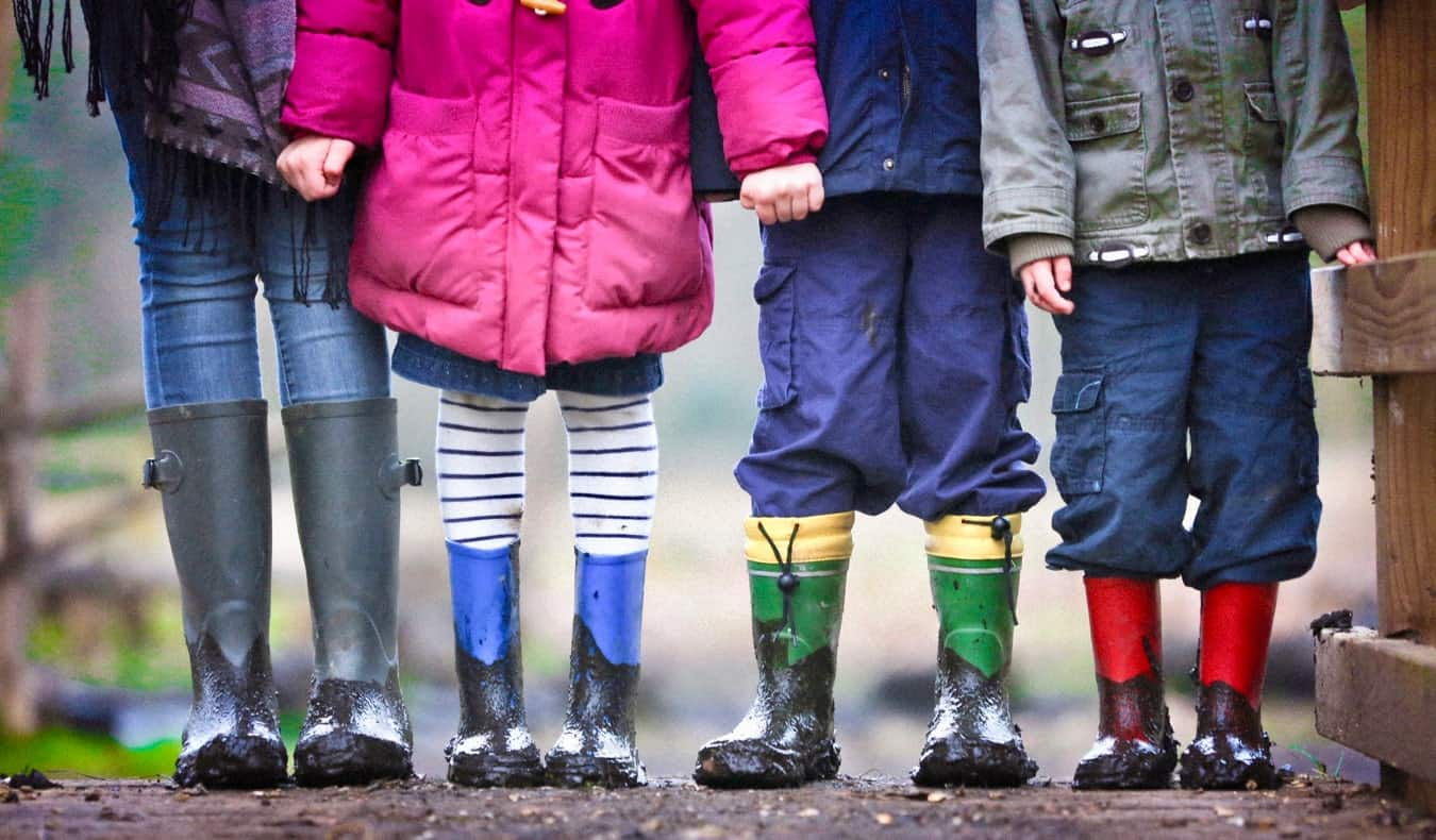 An au pair standing with kids wearing rain boots in the mud