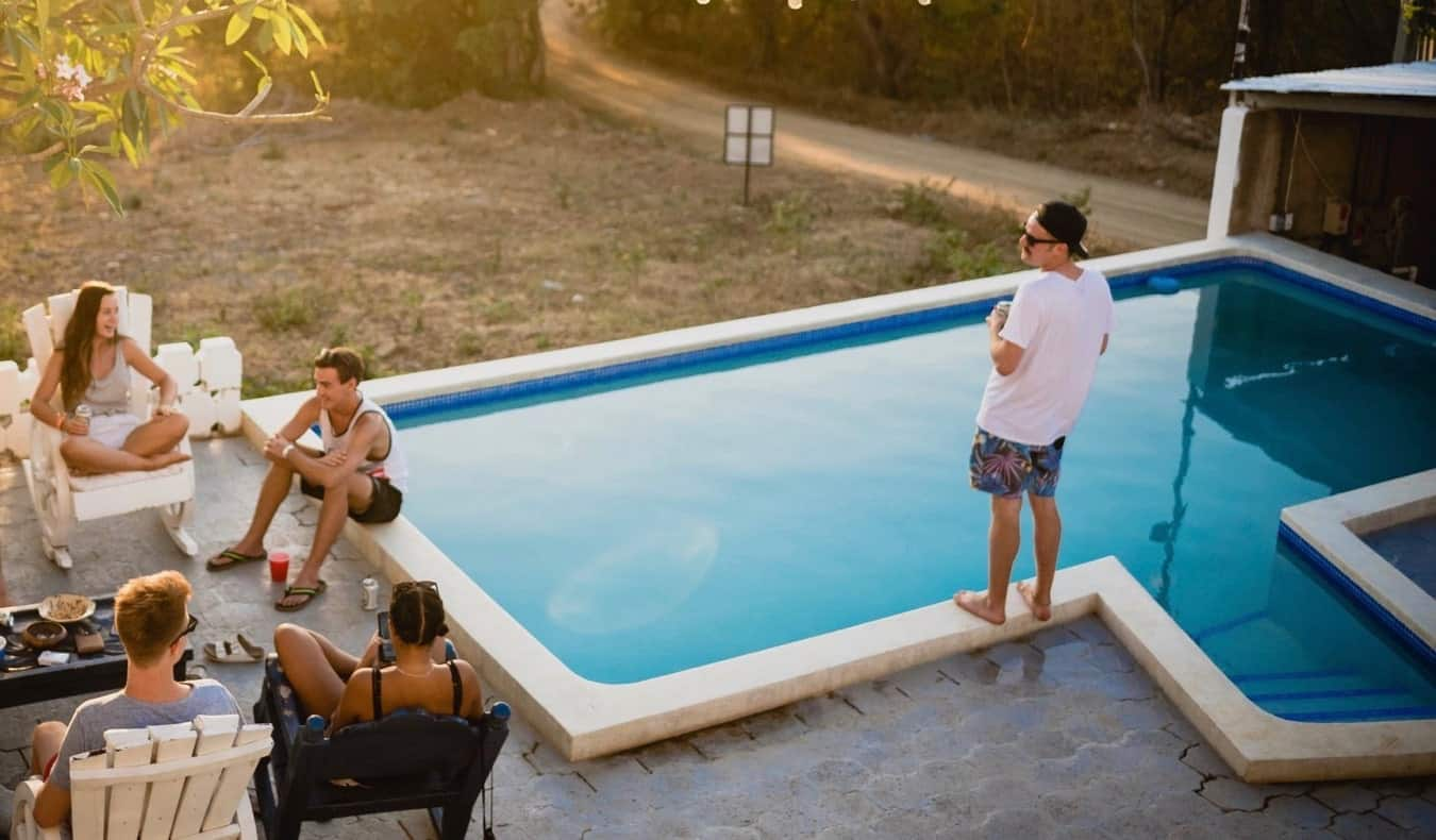 A group of travelers hanging out at the pool at a hostel overseas