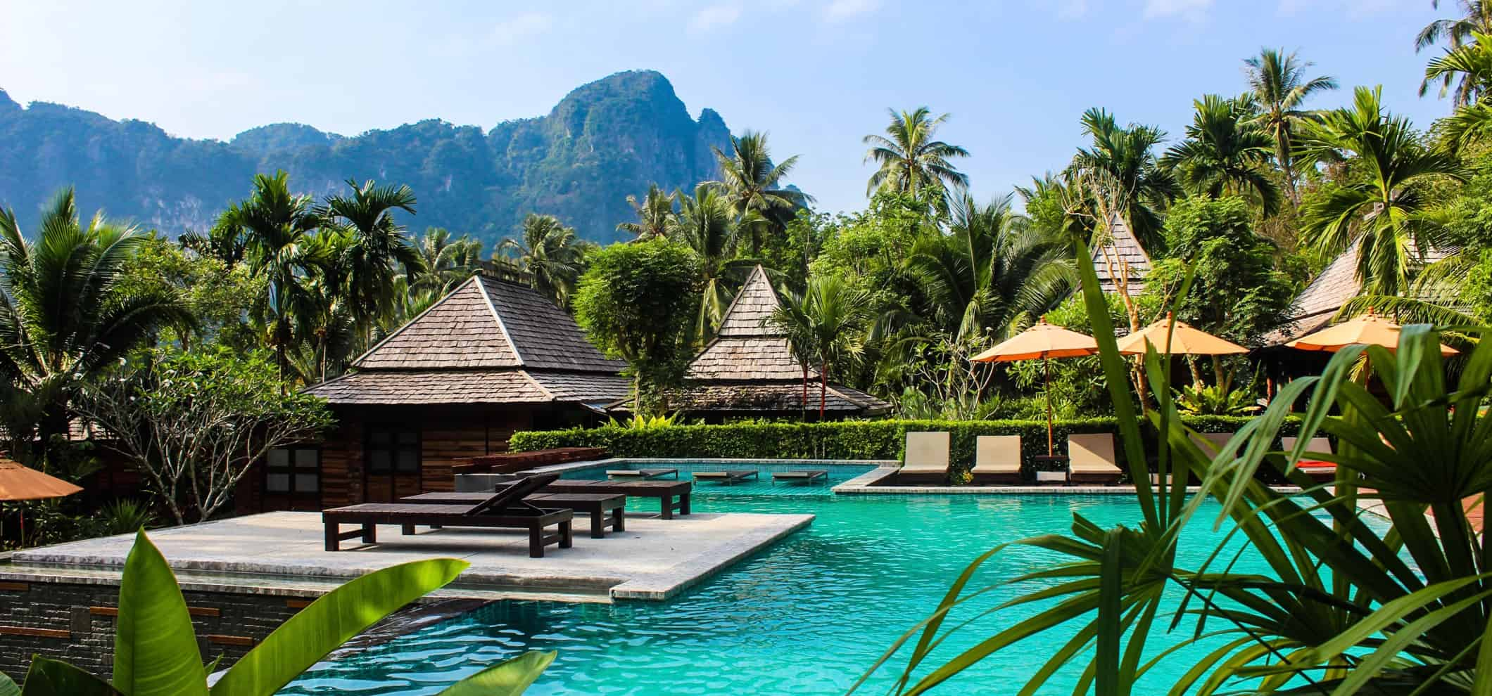 A fancy resort with a pool surrounded by mountains and jungle