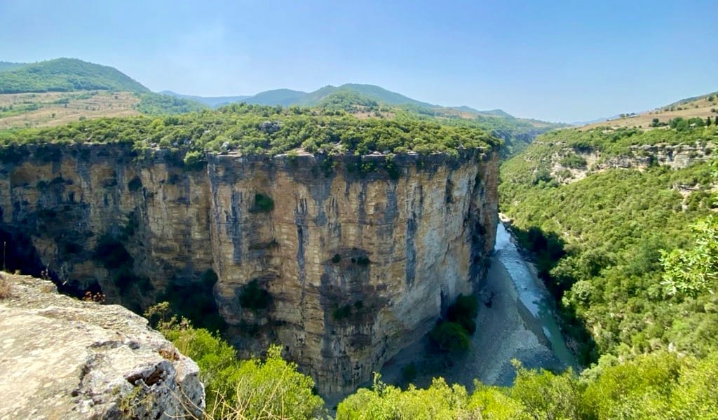 A towering cliff near a river in Albania