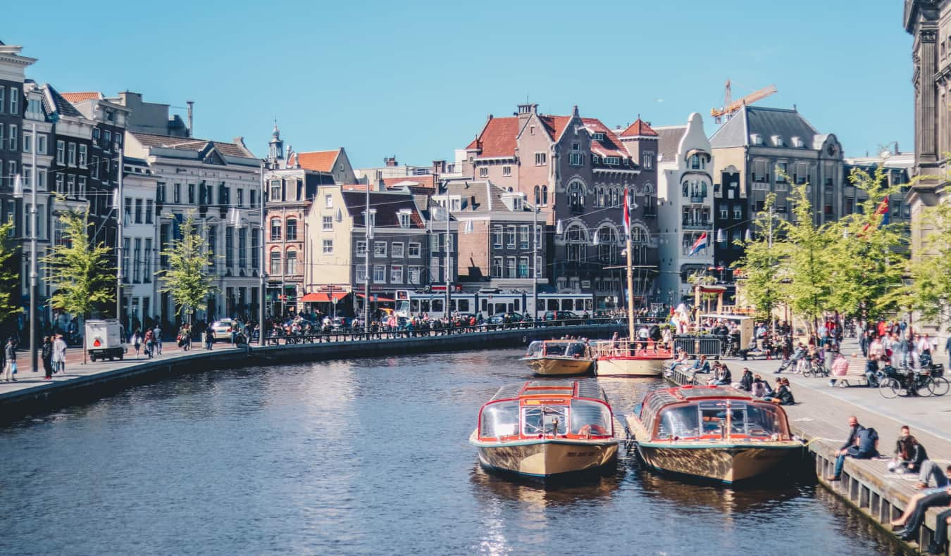A narrow canal with boats in Amsterdam on a sunny summer day