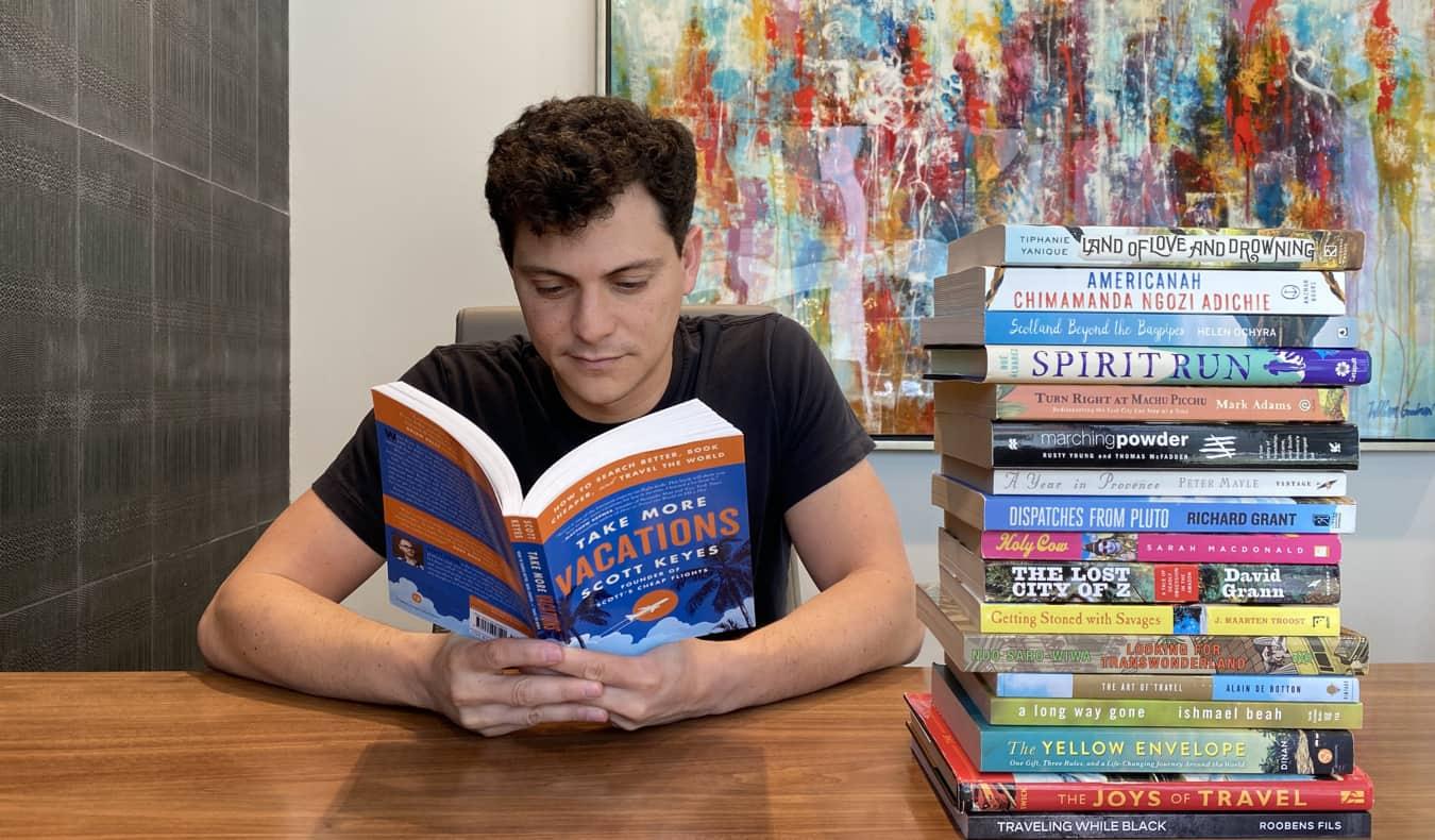 Nomadic Matt reading a travel book at a desk