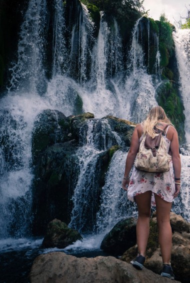 A woman standing near the Kravica Waterfall in Bosnia