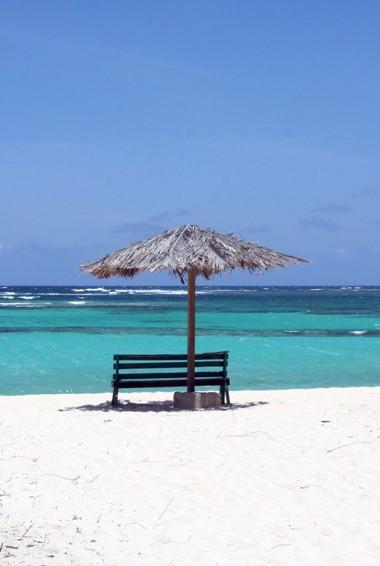A chair and umbrella on the beach in Anegada, BVI