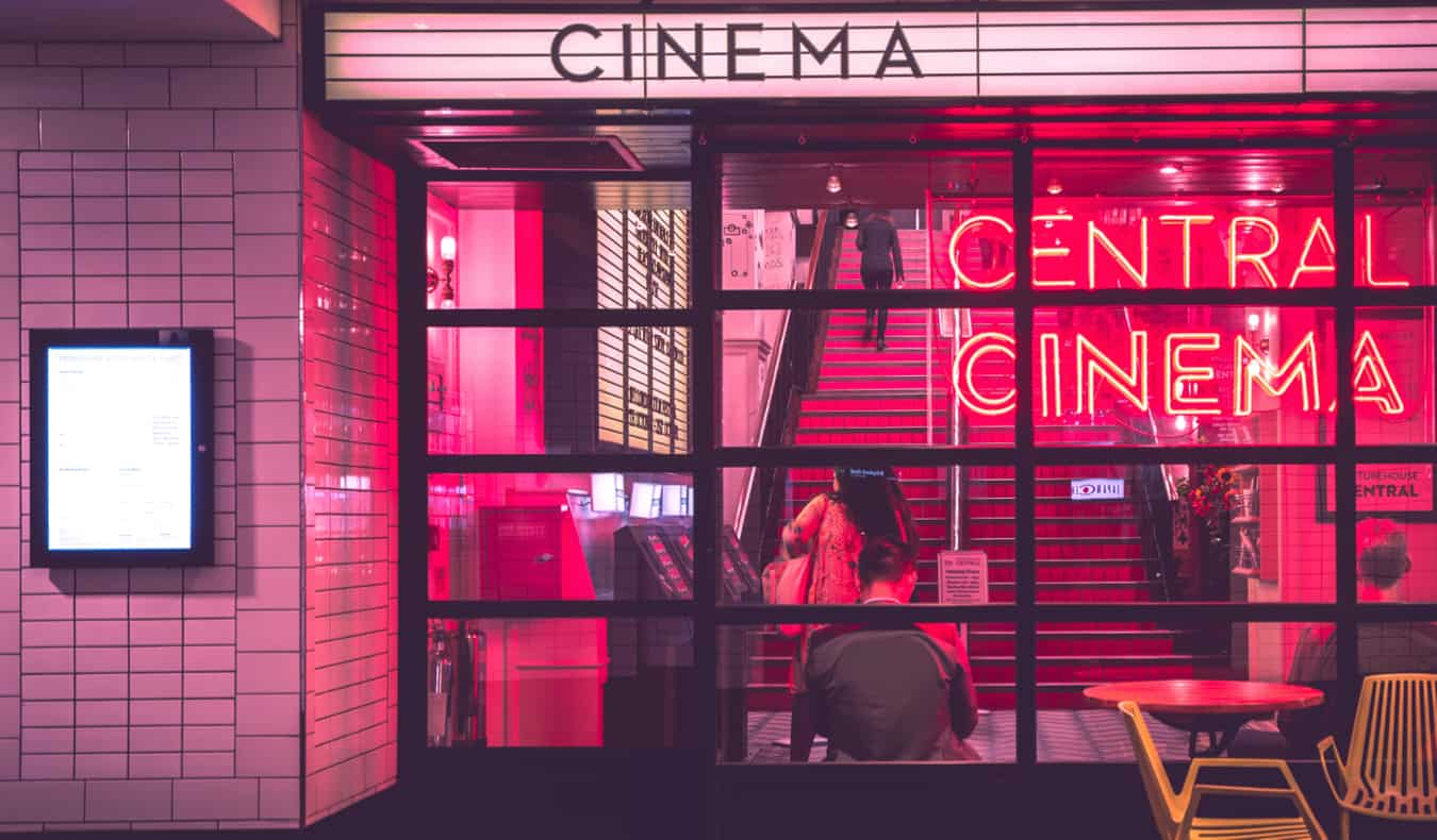 A cinema lit up at night with pink neon light