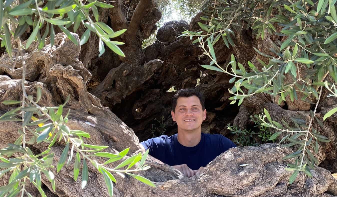 Nomadic Matt peeking through a hole in the rocks of Greece