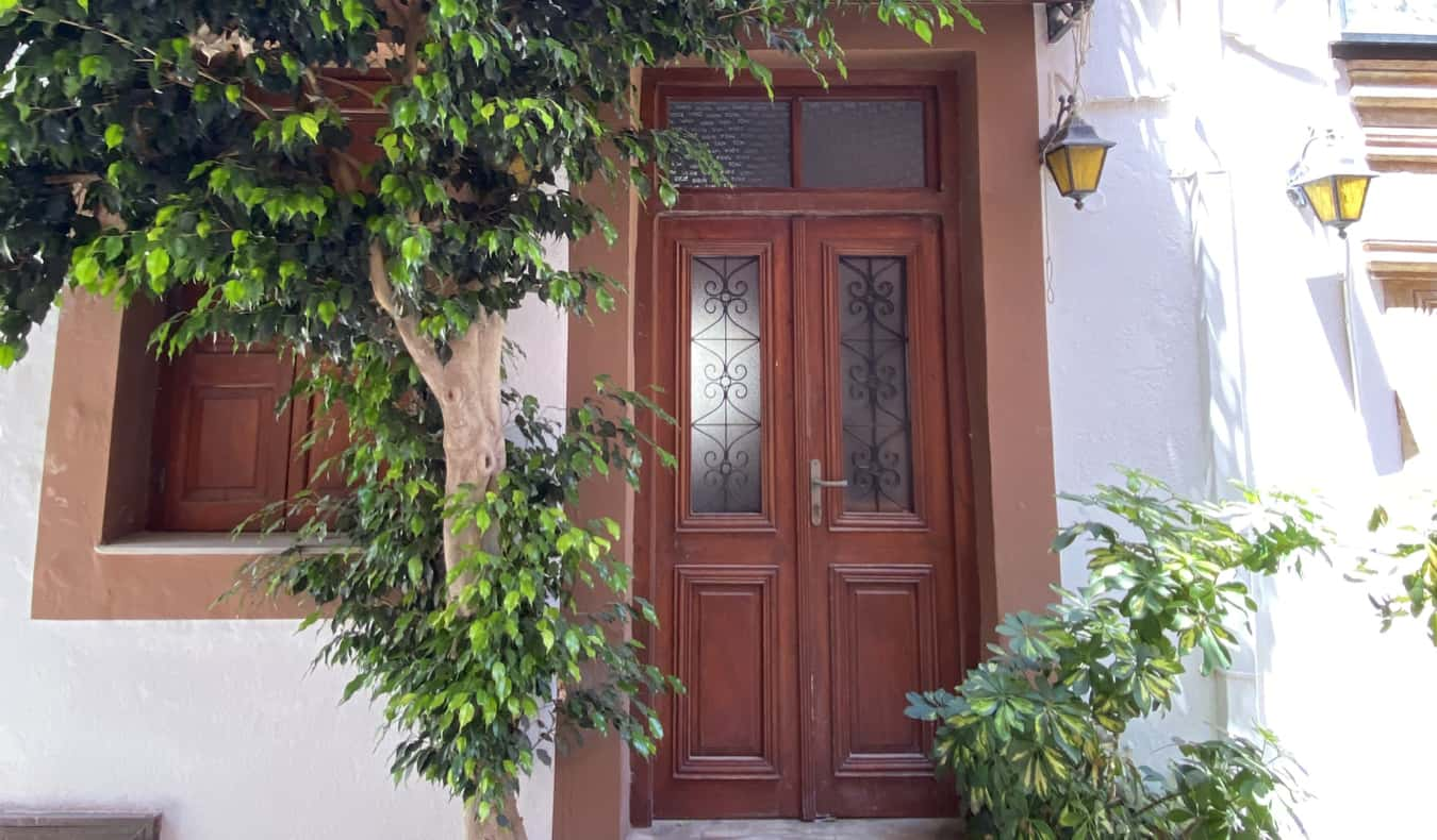 A painted door surrounded by greenery in Crete, Greece